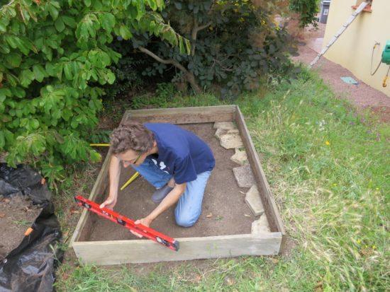 Pour que la réserve d'eau ait la même hauteur partout, il faut que le terrain soit bien de niveau. J'ai donc calé le cadre avec des dalles et remblayé l'un des côtés.